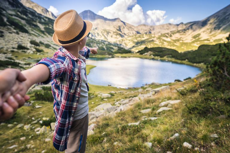 Follow me. Young boy showing the way during hiking activities