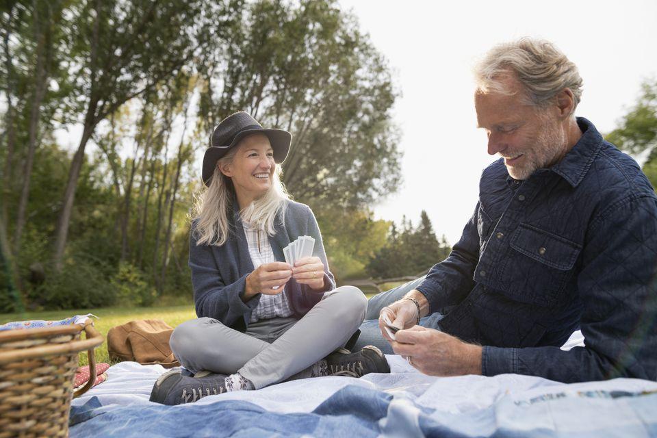 Senior couple playing cards, enjoying picnic in park