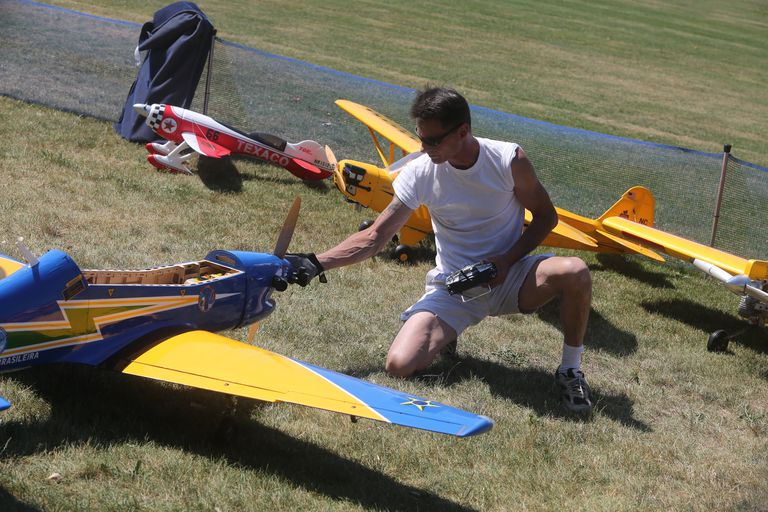 man checking RC toy airplane