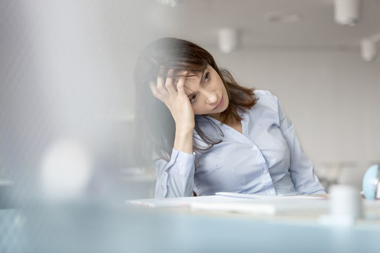 Tired businesswoman with head in hand looking away