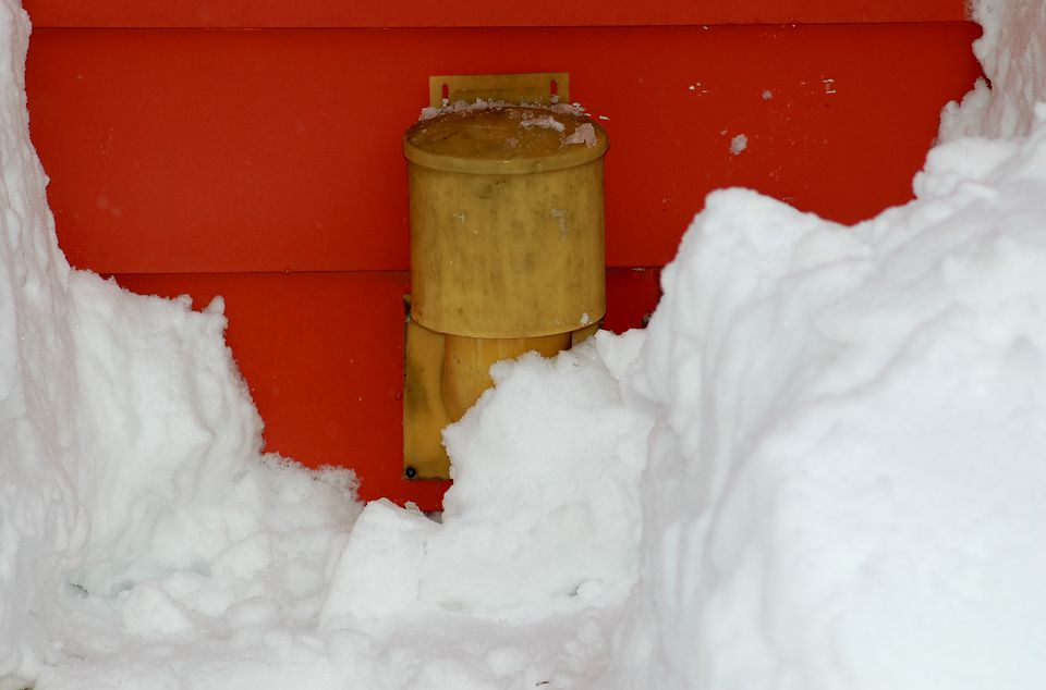 Dryer vent with snow around it, which is a safety hazard.