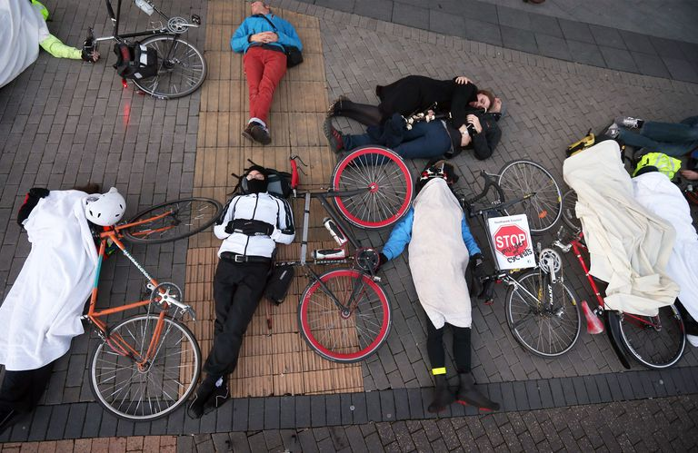 Group of cyclists pose as accident victims in bike safety protest