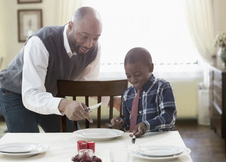 Father and son setting holiday table