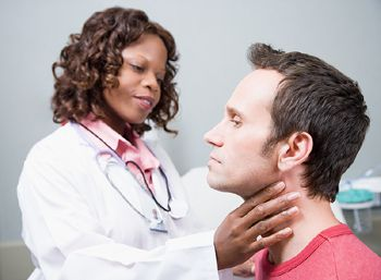 doctor checking neck thyroid