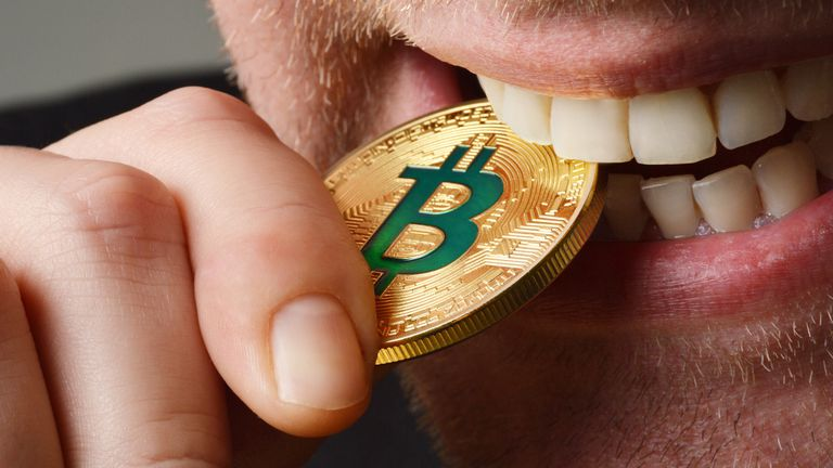 Man biting a Bitcoin coin