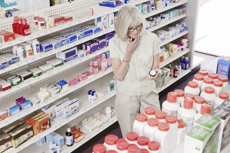 woman looking at over-the-counter meds at pharmacy