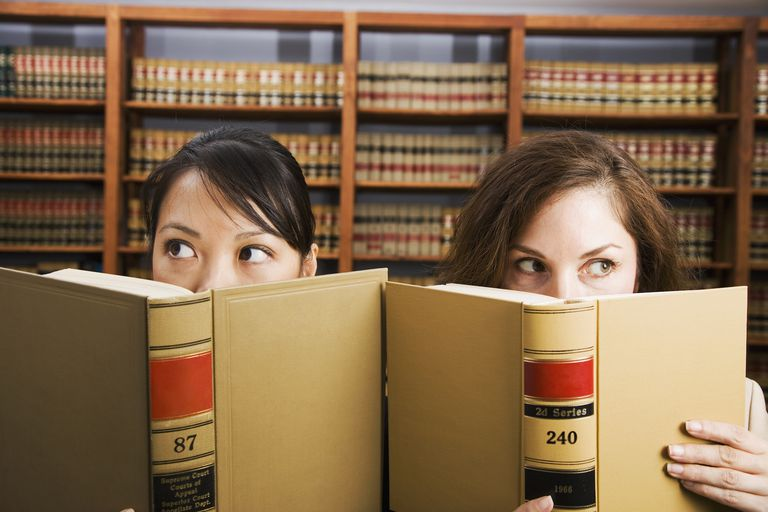 Multi-ethnic women holding library reference book
