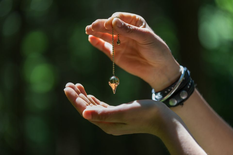 hands with a dowsing pendulum
