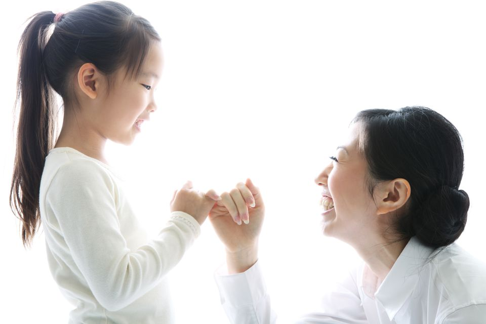Woman and daughter doing a pinky swear promise
