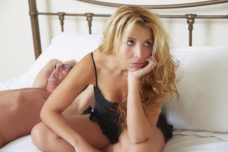 Woman siting on bed, frustrated