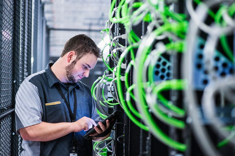 Caucasian technician using digital tablet in server room.