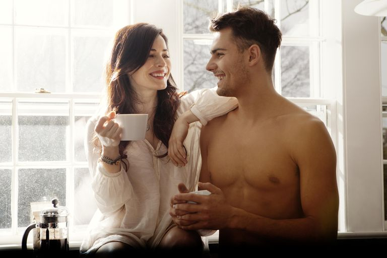 Couple flirting over morning cofee in kitchen