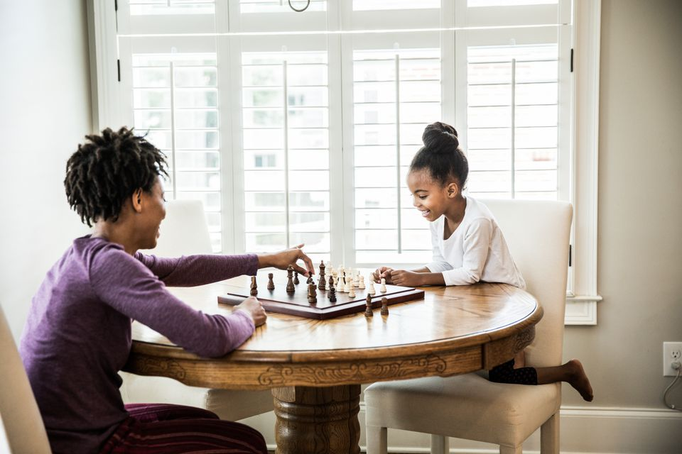 Young girl (6yrs) playing chess with mother