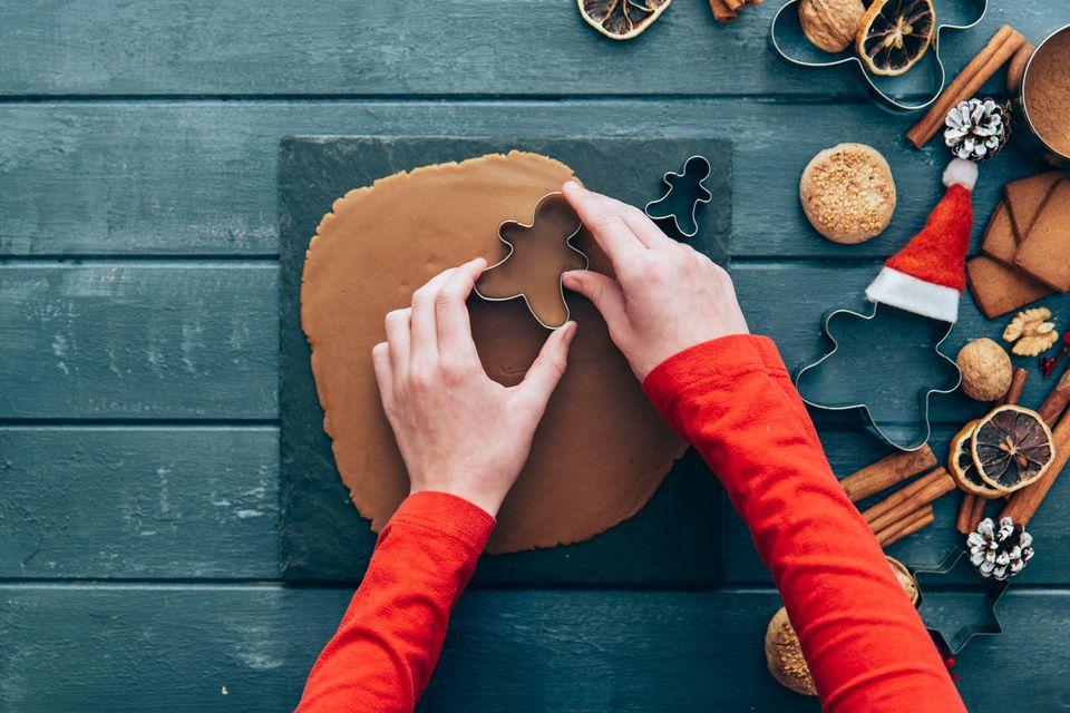 Girl making gingerbread men cookies