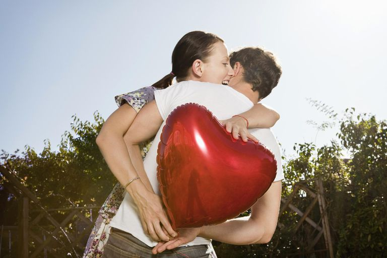 Woman grabs heart shaped balloon from man