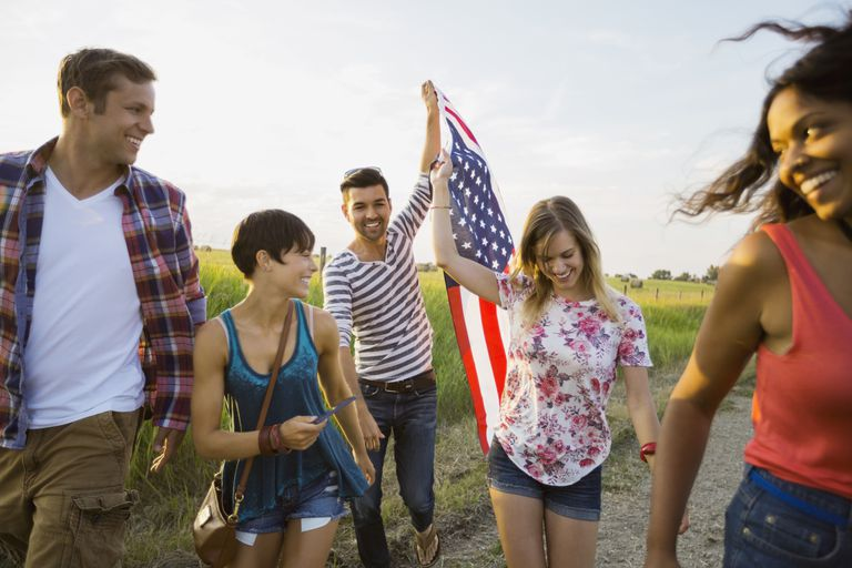 Cheerful friends holding American flag