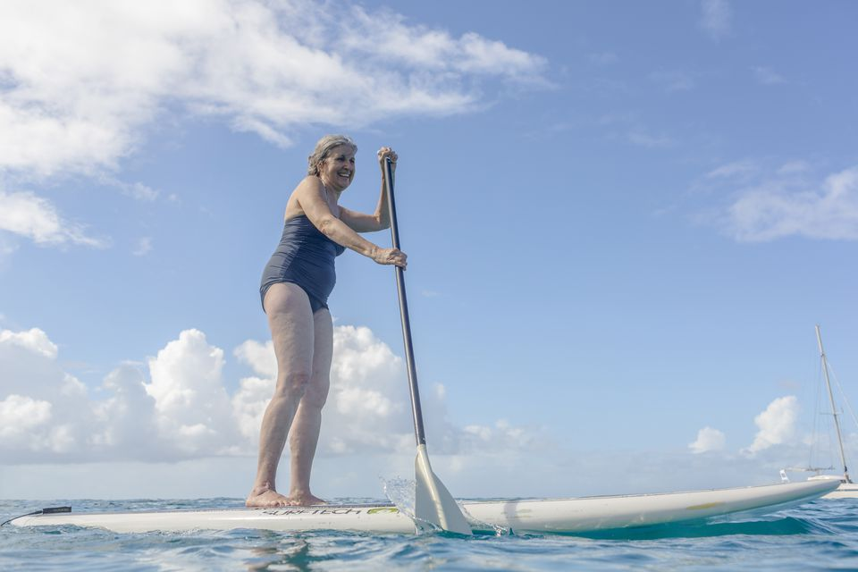 Woman standing on paddle board on ocean