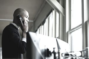 Businessman on phone looking out window of office