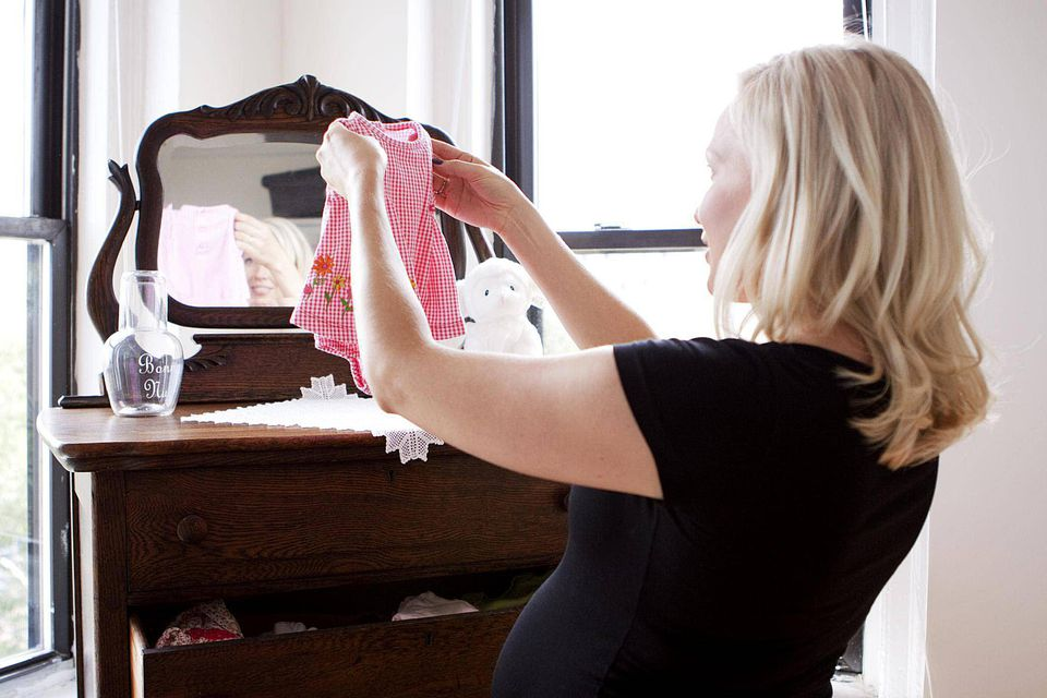 Pregnant woman folding future daughter's clothing