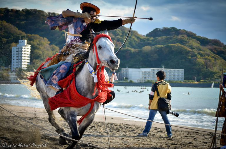 A man competes in a samurai-style archery contest in front of modern beach-front hotel buildings