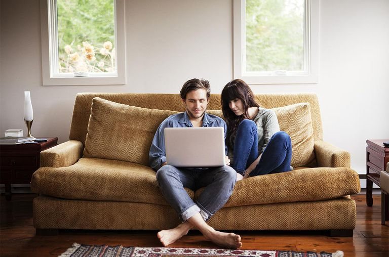 Young Couple On Couch Looking At Computer