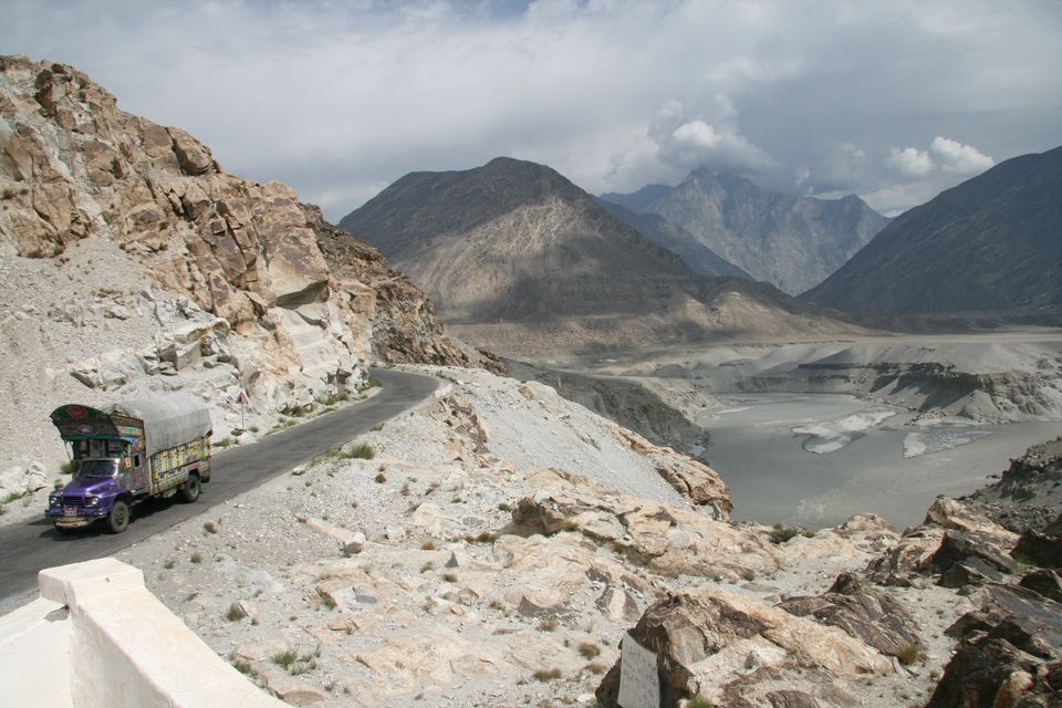 a truck driving along the Karakoram Highway with scenic mountain views in the background