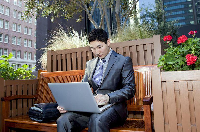 Asian man using a laptop computer outdoors