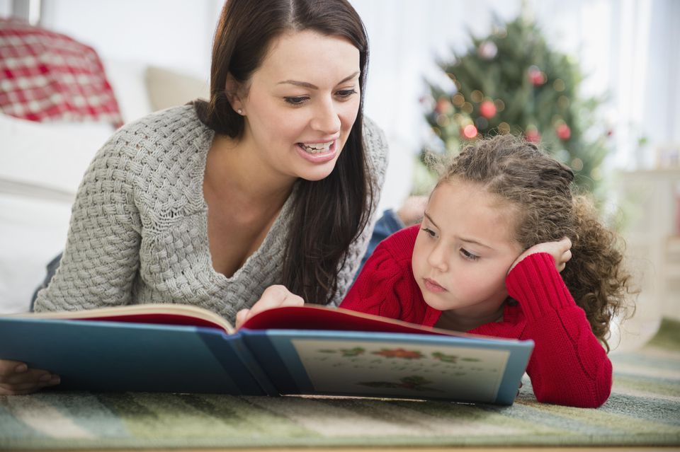 Mother and daughter reading book at Christmas