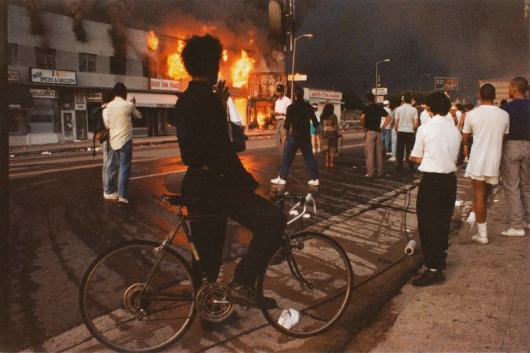 A view of businesses beginning to burn on Pico Boulevard near Hayworth Avenue, onlookers gathering, a young man dressed in black pausing on bicycle watching fire during the Rodney King Riots, and the sky black with smoke in daylight on April 30, 1992 in Los Angeles, California.