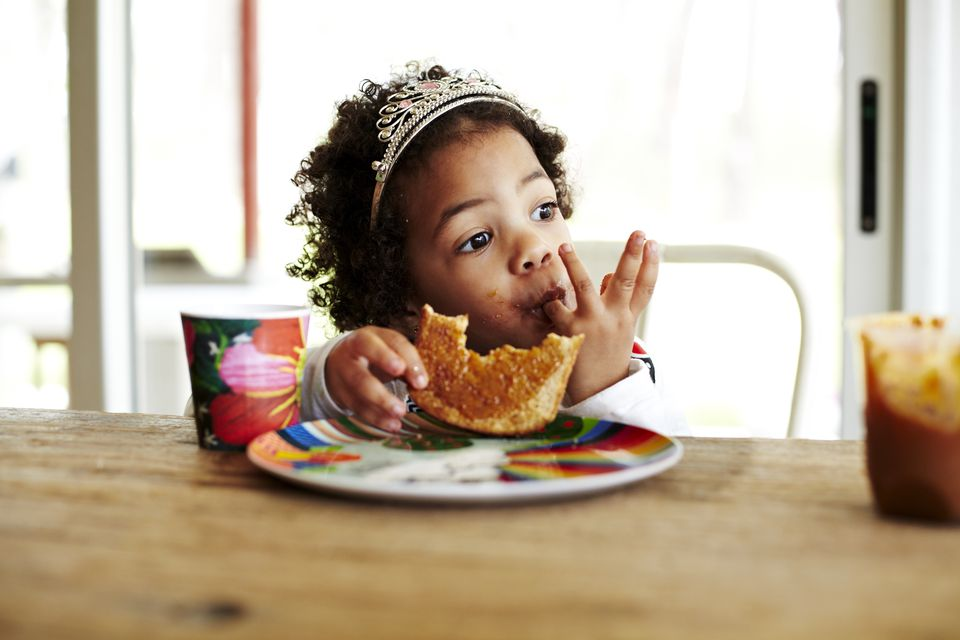 Mixed race girl eating lunch at table