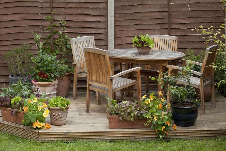 Wooden table, chairs and fruit and vegetables in plant pots on patio decking in garden