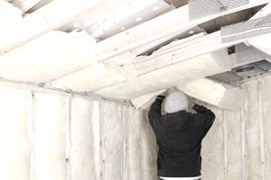 Worker Installing Fiberglass Batt Insulation between Roof Trusse