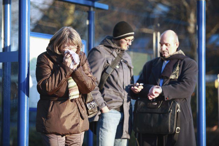Woman sneezing at bus stop