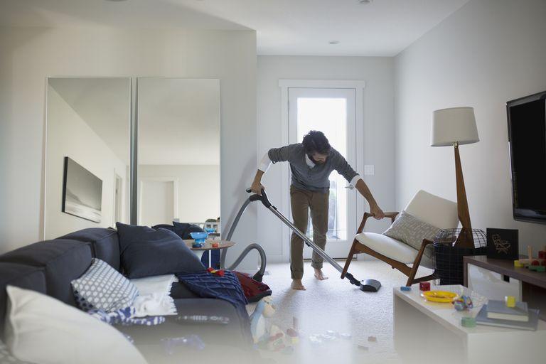 Man vacuuming under chair in living room