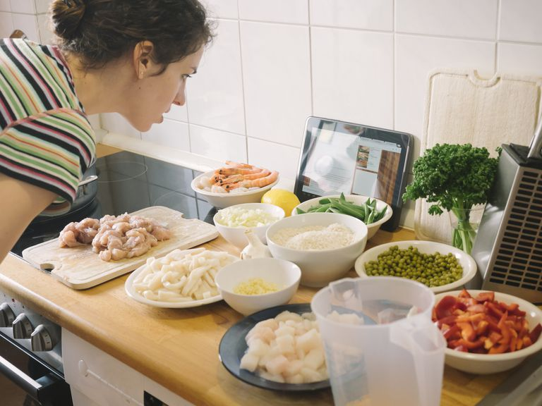 Woman looking at recipe on tablet while cooking