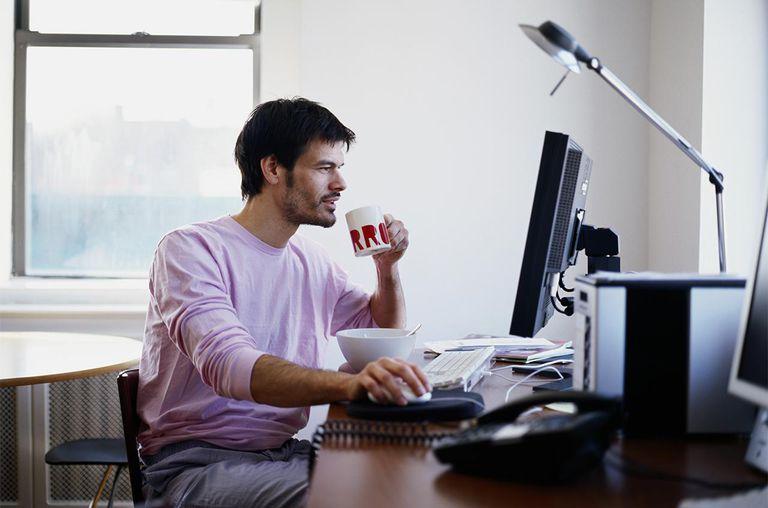 Man at computer, holding mug, side view