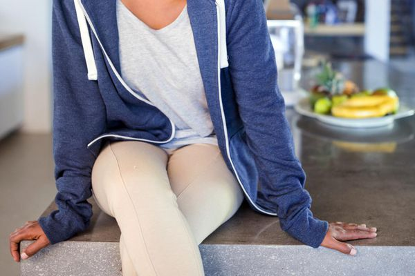 Woman sitting in kitchen looking into camera