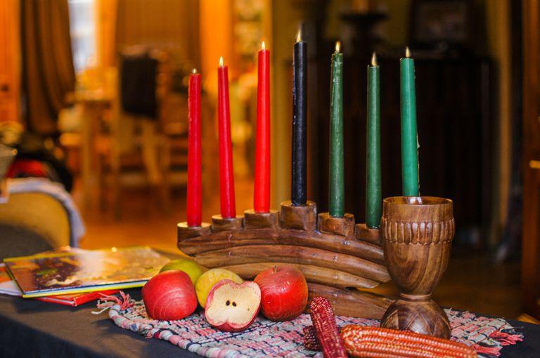 Lit Kinara candles slided apple and ears of corn for Kwanzaa celebration