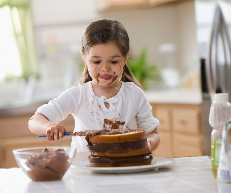 Young girl frosting chocolate cake