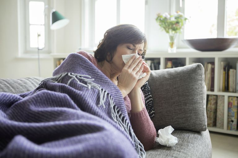 Woman lying on the couch with the flu