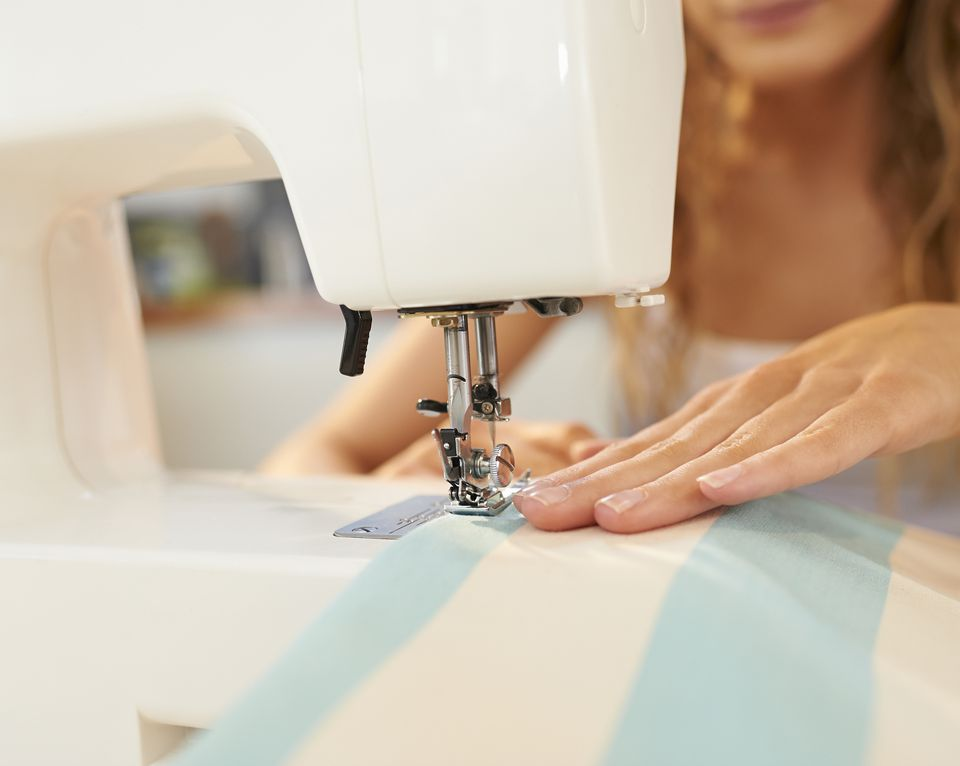 Woman using sewing machine, close up.