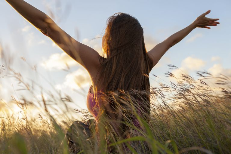 Woman with her hands outstretched soaking up the sun