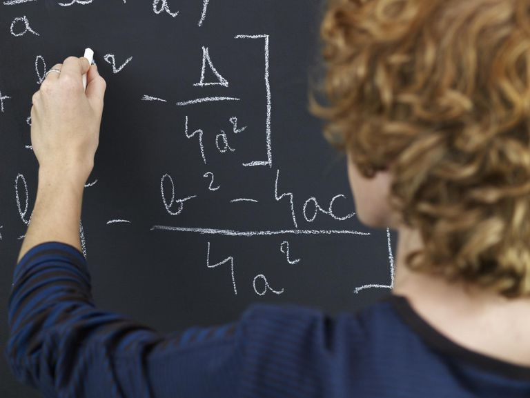 High School Student Solving Equation on Blackboard