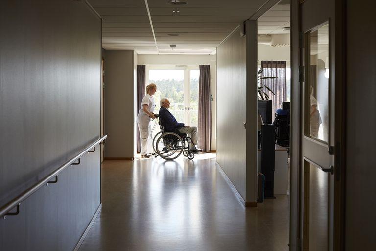 Full length side view of female nurse pushing senior man on wheelchair at hospital corridor