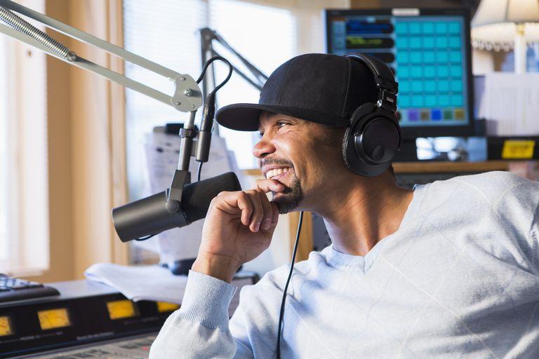Mixed race disc jockey smiling in studio