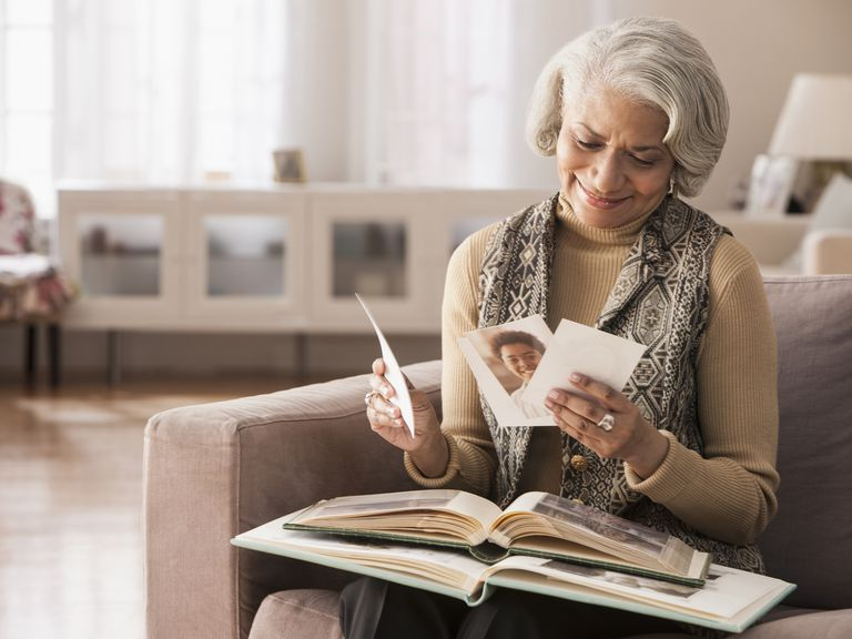 Older Black woman looking at photographs