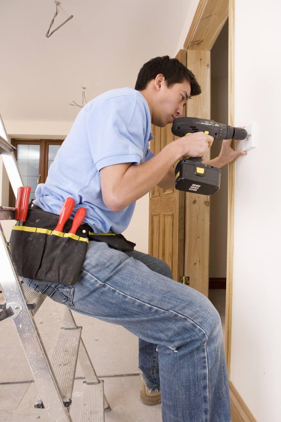 Electrician drilling outlet in wall