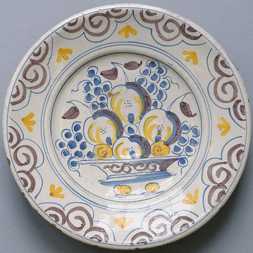 A majolica plate decorated with a bowl of fruit.