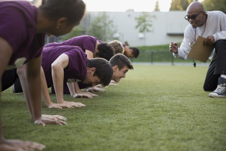 Physical education teacher encouraging students doing push-ups