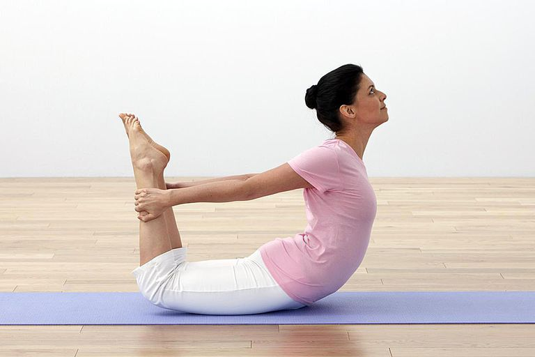 Woman performing rocking bow yoga pose on exercise mat, side view